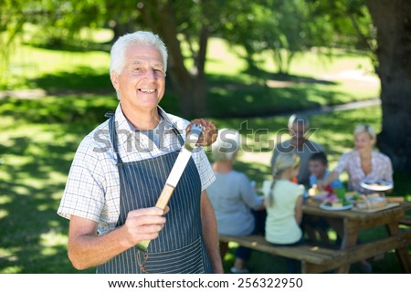 Happy grandfather doing barbecue on a sunny day - stock photo