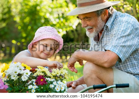 Happy grandfather with his granddaughter  in the garden - stock photo