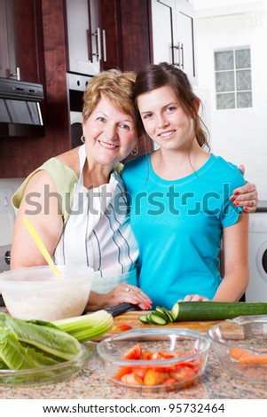 happy grandma and teen granddaughter portrait in kitchen - stock photo