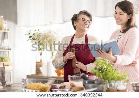 Happy grandma cooking with her granddaughter in modern kitchen