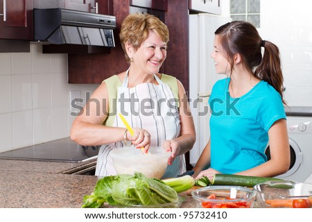 happy grandma talking to granddaughter in kitchen while cooking
