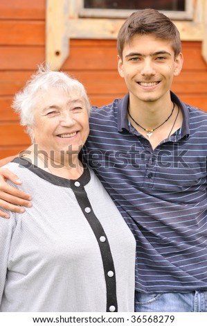 Happy grandmother and grandson in front of house