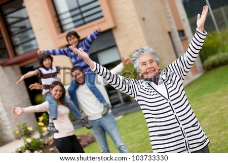 Happy grandmother at the backyard of her new house - stock photo