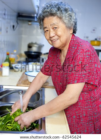 happy grandmother  cooking healthy foods in kitchen - stock photo