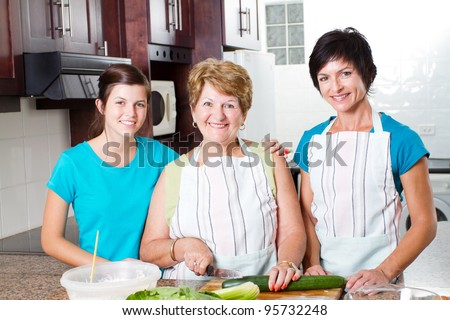 happy grandmother cooking with her daughter and granddaughter in kitchen - stock photo