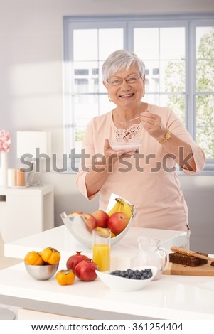 Happy grandmother eating breakfast cereal by kitchen counter full of fruits. - stock photo