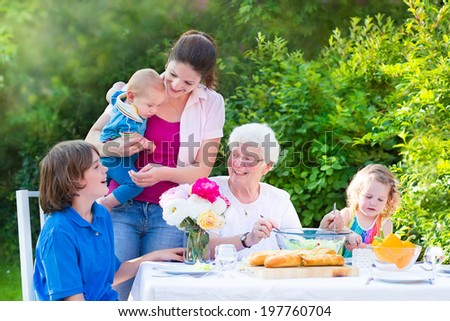 Happy grandmother enjoying sunny summer day having lunch with family - young woman and three children, teen age boy, toddler girl and a little baby, eating grilled meat, salad and bread in the garden - stock photo