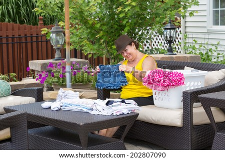 Happy Grandmother folding her granddaughters clothes with a beaming smile of pleasure as she holds a garment up in front of her as she sits enjoying the summer sunshine on the patio of her home - stock photo