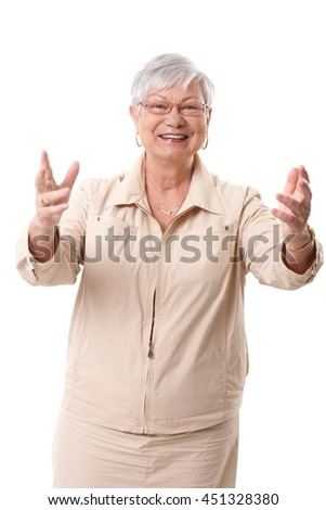 Happy grandmother greeting someone with arms wide open.