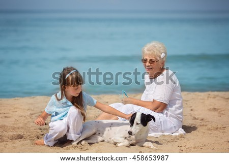 Happy grandmother has fun with granddaughter and her pet on the seaside