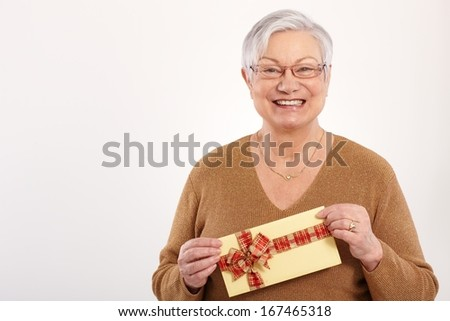 Happy grandmother holding present in hand, smiling, looking at camera. - stock photo