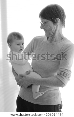 Happy grandmother holds her grandchild at home. Concept photo of newborn, baby, grandmother, grand motherhood, senior,retirement, lifestyle (BW) - stock photo