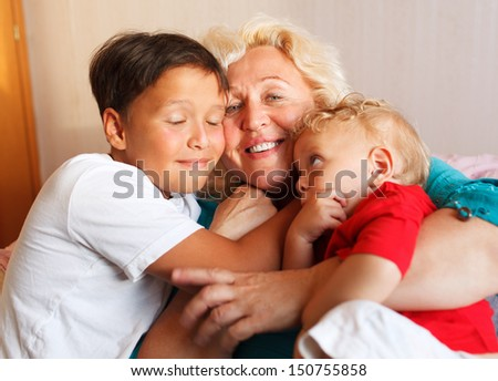 Happy grandmother hugging with her grandchildren at home - stock photo