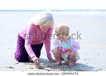 Happy grandmother playing with her granddaughter, cute toddler girl, at the beach drawing on the sand - stock photo