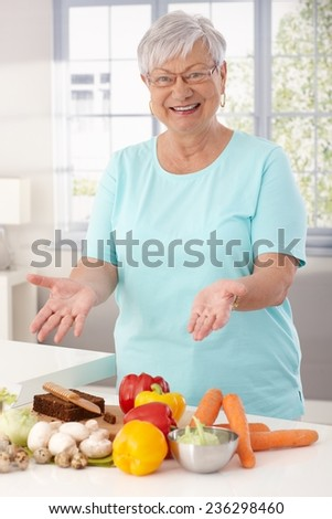 Happy grandmother showing healthy raw materials on kitchen counter, smiling, looking at camera. - stock photo