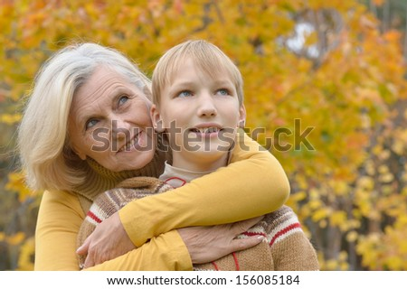Happy grandmother with boy resting in the autumn park - stock photo