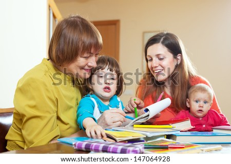 Happy  grandmother with daughter and grandchildren drawing on paper at home. Focus on mature - stock photo