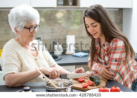 Happy grandmother with granddaughter preparing a salad in the kitchen. - stock photo