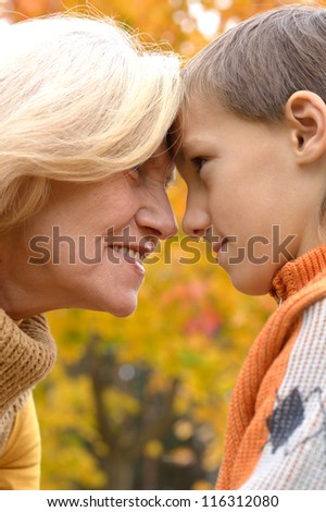 happy grandmother with her boy resting in the autumn park - stock photo