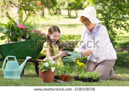 Happy grandmother with her granddaughter gardening on a sunny day - stock photo