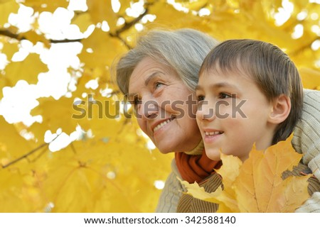 Happy grandmother with her grandson for a walk in a autumn park - stock photo