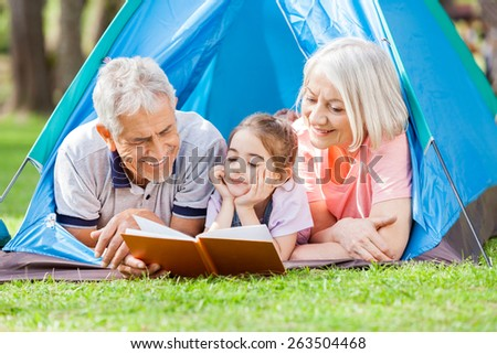 Happy grandparent with granddaughter reading book at campsite in park - stock photo