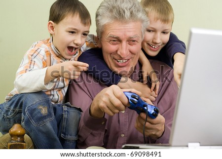 happy grandparent with their grandchildren play on the computer