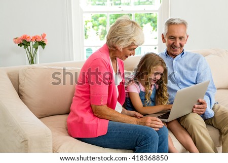Happy grandparents and girl using laptop while sitting on sofa - stock photo