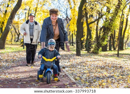 happy grandparents and grandchild have fun and play in park - stock photo