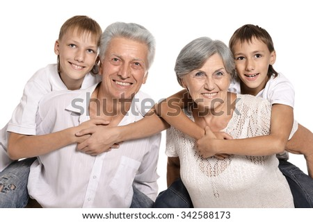 Happy grandparents and their two grandchildren on a white background