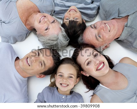 Happy grandparents, parents and children lying on floor with heads together
