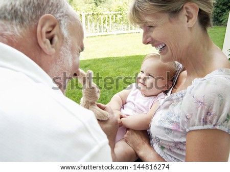 Happy grandparents playing with granddaughter in garden - stock photo