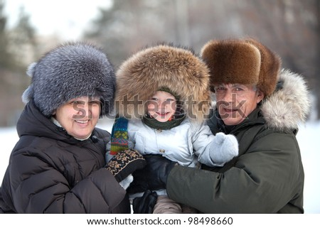 Happy grandparents with a cute toddler boy in their arms on a cold winter day - stock photo