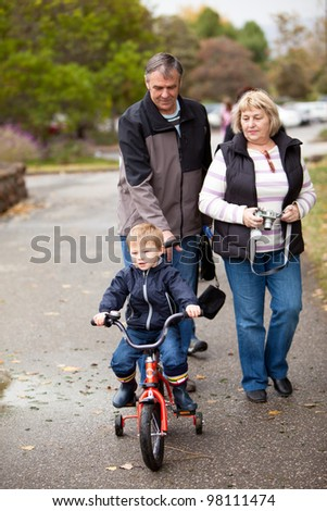 Happy grandparents with a toddler boy on a bike