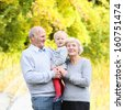 Happy grandparents with little baby granddaughter in beautiful autumn park - stock photo