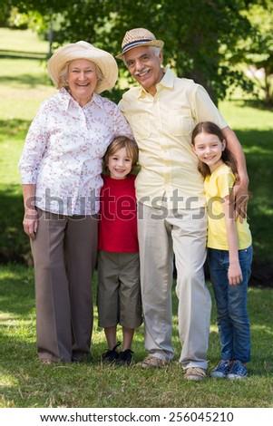 Happy grandparents with their grandchildren at the garden on a sunny day - stock photo