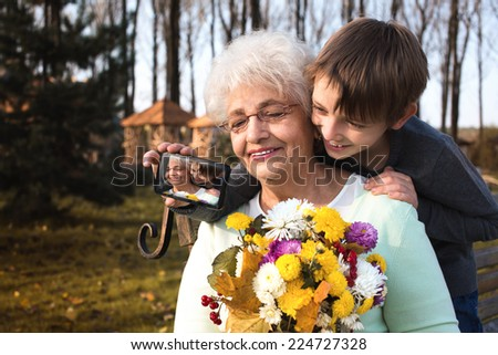 happy grandson with grandmother taking picture in the autumn park - stock photo