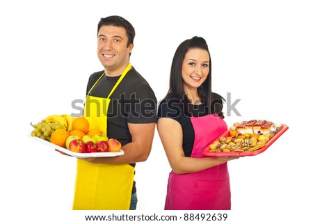 Happy greengrocer and confectioner showing their products on plateau isolated on white background
