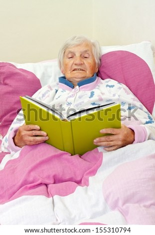 Happy grey haired senior woman reading a book - stock photo