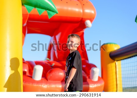 Happy grinning little boy at a fair or a kids playground standing in front of an inflatable jumping castle in the shape of a hippo - stock photo