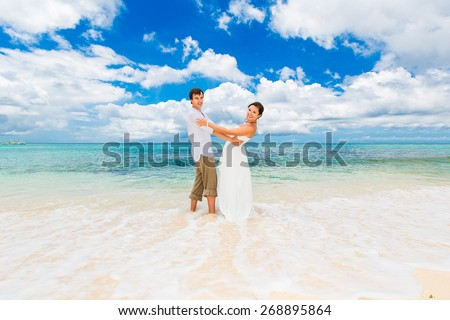 Happy groom and bride having fun on the sandy tropical beach. Wedding and honeymoon concept.