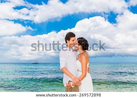Happy groom and bride having fun on the sandy tropical beach. Wedding and honeymoon concept. - stock photo