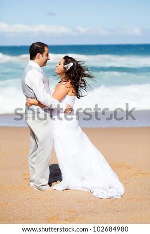 happy groom and bride hugging on beach - stock photo