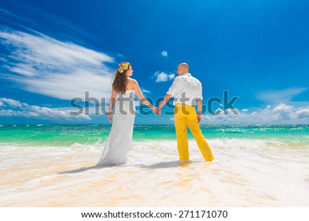 Happy groom and bride standing with his back to the viewer on the sandy tropical beach and holding hands. Wedding and honeymoon in the tropics. - stock photo