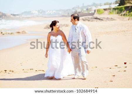 happy groom and bride walking on beach - stock photo