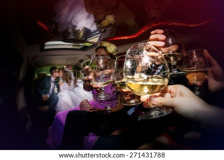 Happy groom and the bride  with cheerful friends are sitting inside the wedding limo waving - stock photo
