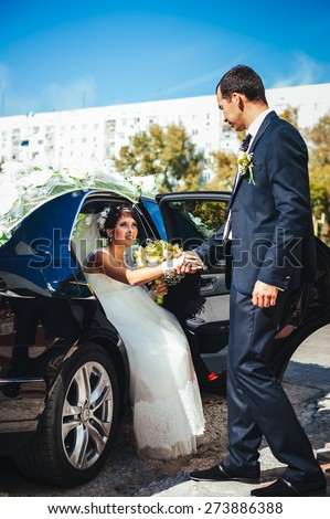 Happy groom helping his bride out of the wedding car. newly wedded standing near wedding car. - stock photo