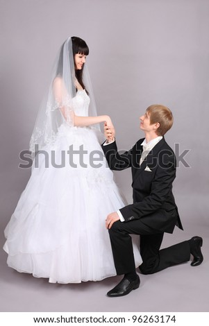 Happy groom kneels and holds beautiful bride hand in studio on gray background - stock photo