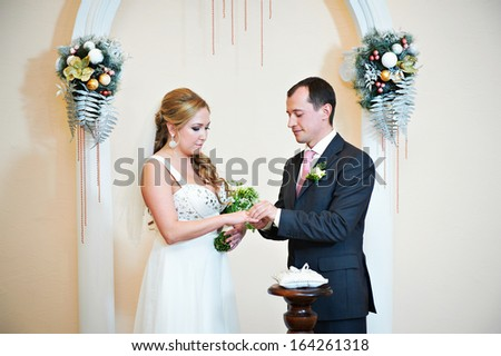 Happy groom wears wedding ring his bride. Solemn registration of marriage. - stock photo
