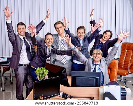 Happy group business people with hand up in office. Venetian blinds background. - stock photo